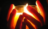 Hands holding a lit candle in a jar container.