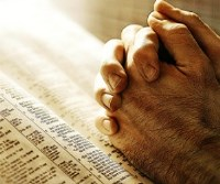 Hands clasped in prayer over a bible