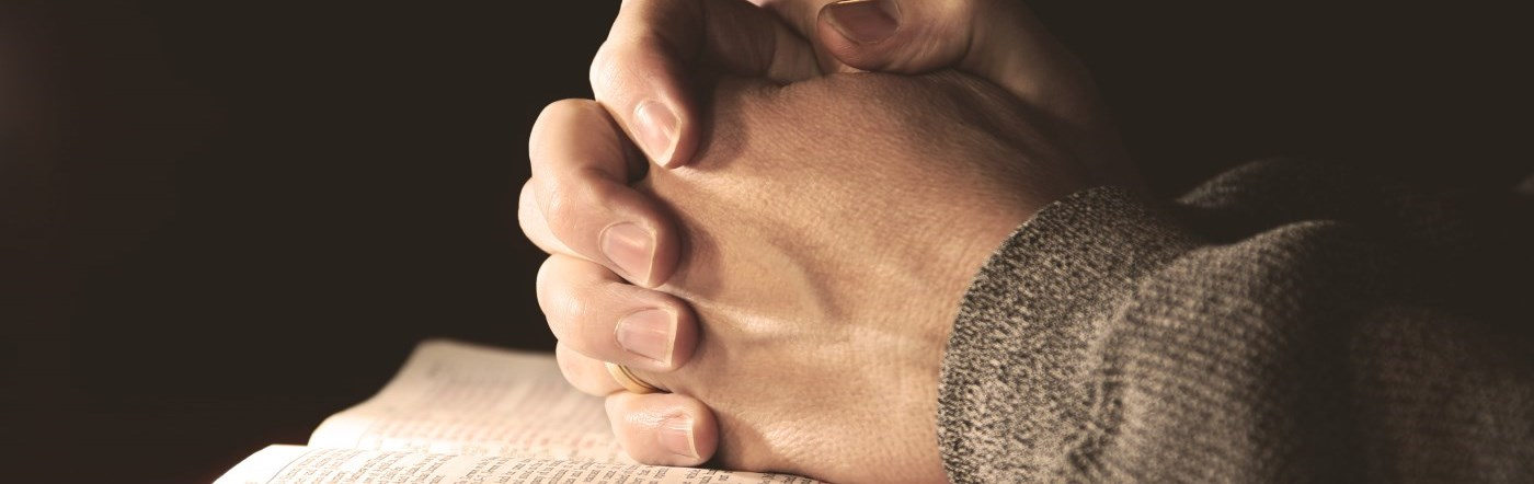 Hands at prayer over a bible.